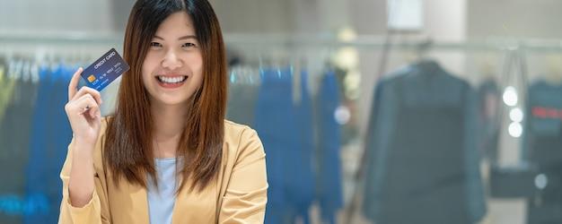Sztandar azjatycka kobieta trzyma i przedstawia kartę kredytową dla zakupy online w domu towarowym