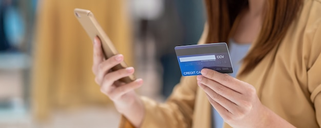 Sztandar azjatycka kobieta używa kredytową kartę z telefonem komórkowym dla online zakupy w domu towarowym