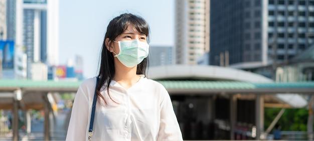 Sztandar bizneswoman w białej koszuli idzie do pracy w mieście zanieczyszczenia, nosi maskę ochronną