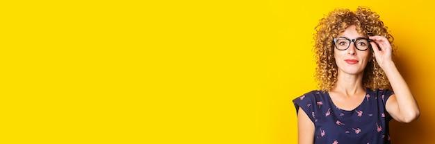 Sztandar uśmiechający się kręcone włosy młoda kobieta w przezroczystych okularach na żółtym tle.