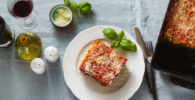 Sztandar wegańskiej lasagne z soczewicą i zielonym groszkiem w blasze do pieczenia na stole z niebieskim lnianym obrusem. i czerwone wino w kieliszkach