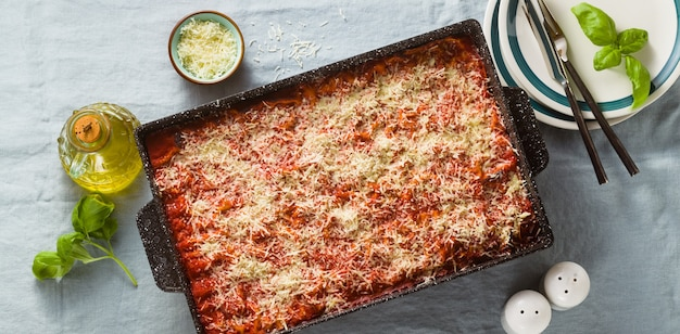 Sztandar wegańskiej lasagne z soczewicą i zielonym groszkiem w blasze do pieczenia na stole z niebieskim lnianym obrusem.