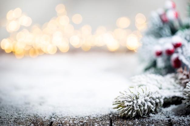 Sztandar z dekoracjami świątecznymi na śniegu z gałęziami jodły i zimowymi światłami bożonarodzeniowymi