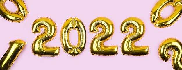 Sztandar ze złotymi balonami foliowymi na różowym tle numery złote balony na różowej ścianie nowy rok