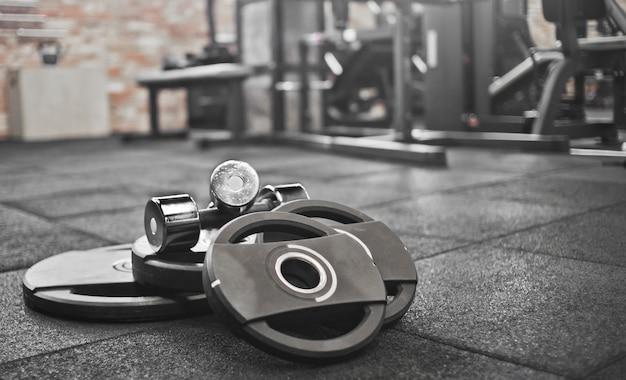 Sztanga, hantle leżą na podłodze na tle siłowni. wolny trening siłowy. potężny trening funkcjonalny
