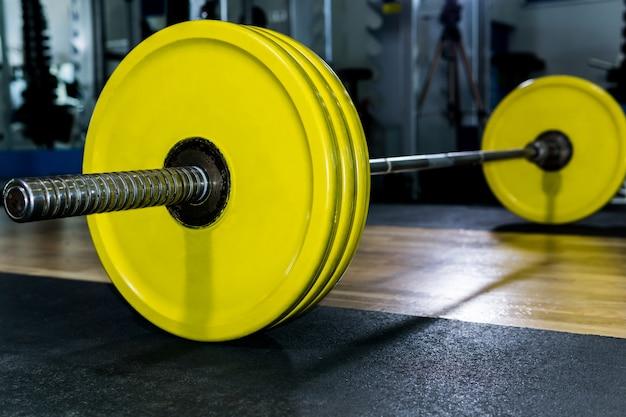 Sztanga z jasnożółtymi płytkami na siłowni przed maszyną do ćwiczeń