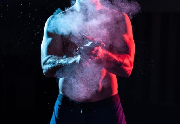 Sztangista klaszcze w dłonie talkiem i przygotowuje się do treningu w czerwonym, niebieskim, gradientowym neonowym świetle.