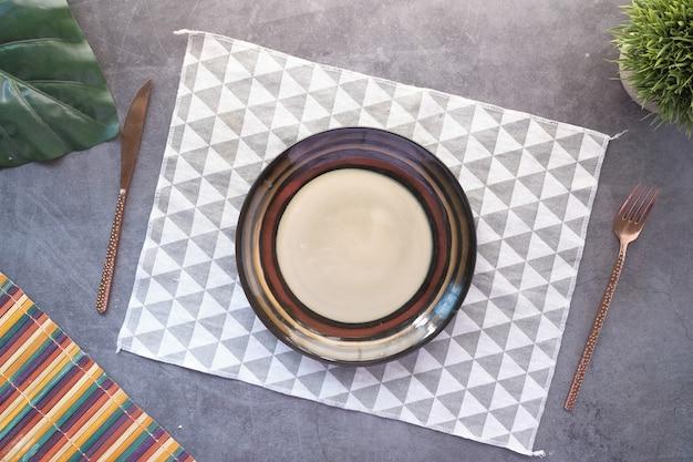 Sztućce i pusty talerz na drewnianym