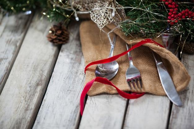 Sztućce owinięte christmas motywu na drewnianym stole