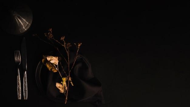 Sztućce w pobliżu gałązki i liści