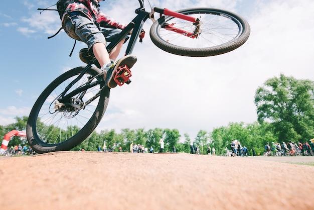 Sztuczki na rowerze. młody człowiek skacze na rowerze górskim. pojęcie sportu rowerowego
