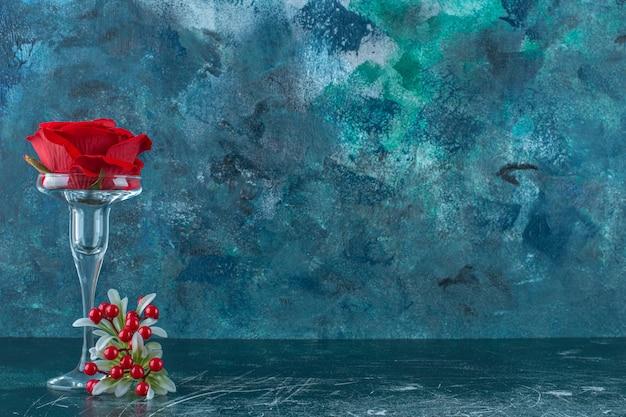 Sztuczna czerwona róża w szklanym cokole, na niebieskim tle.
