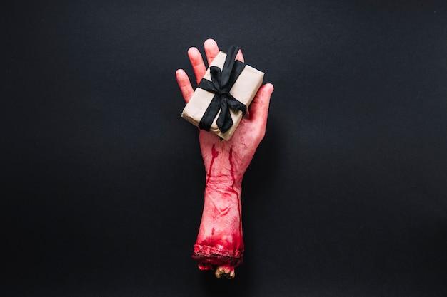 Sztuczna odcięta ręka z upakowaną prezentem