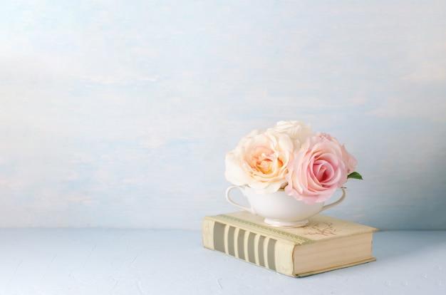 Sztuczna różowa róża kwitnie w białej filiżance z starą książką na błękicie