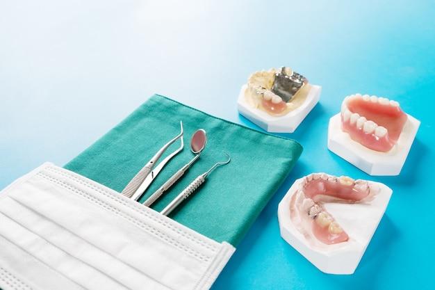 Sztuczna zdejmowana proteza częściowa lub tymczasowa proteza częściowa na niebieskim podłożu.