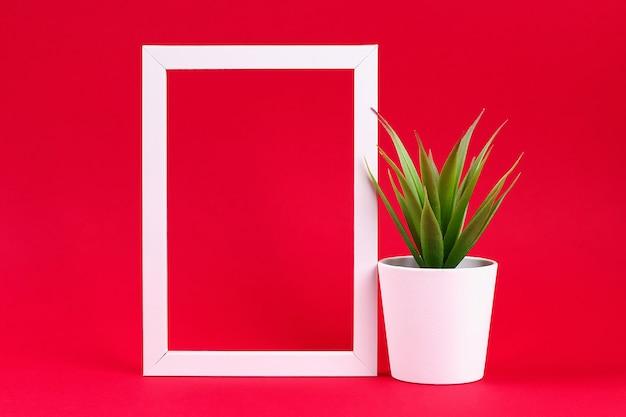 Sztuczna zielona trawa w białym małym garnku w białej ramce na czerwonym tle bordowym.