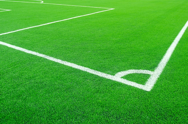 Sztuczna zielona trawa z białymi paskami na boisku piłkarskim