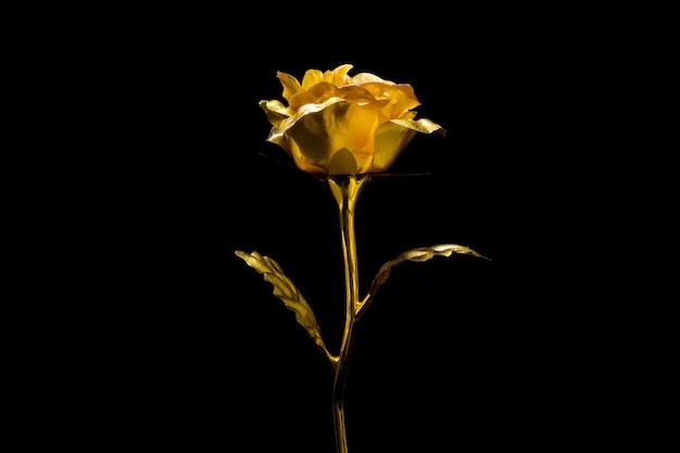 Sztuczna złota róża na czarnym tle.
