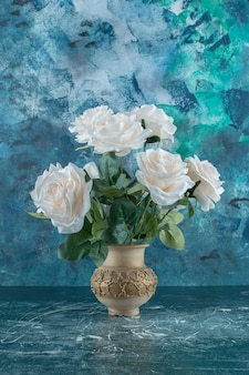 Sztuczne białe róże w wazonie, na niebieskim tle.