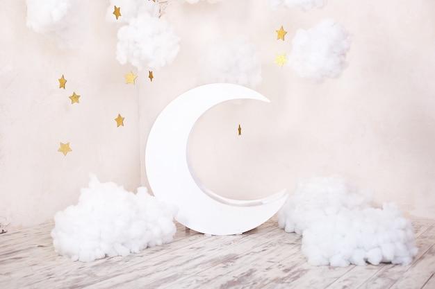 Sztuczne dekoracje z księżycem i gwiazdami. vintage dekoracje. stylowy pokój dziecięcy w stylu vintage z drewnianym księżycem i tekstylnymi chmurami. vintage pokój dziecięcy z księżycem. pokój w stylu skandynawskim