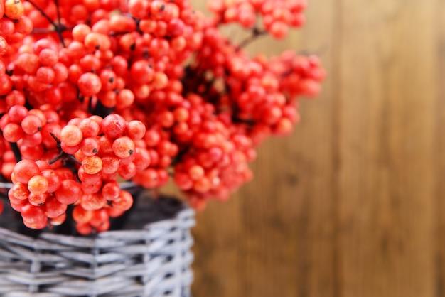 Sztuczne jagody, w wiklinowym wazonie, na drewnianym tle