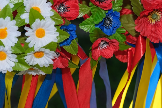 Sztuczne kwiaty i wstążki słowiańskiego wieńca ukraińskiego dla dziewczynek z bliska makrofotografia