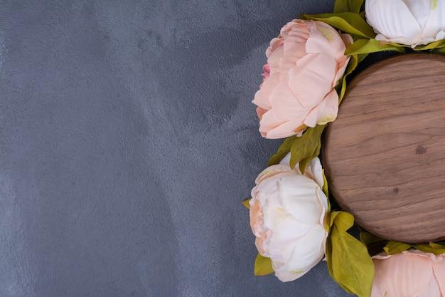 Sztuczne kwiaty wokół okrągłego drewna na niebiesko.