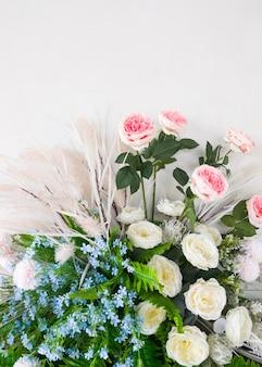 Sztuczne kwiaty z tkaniny i tworzywa sztucznego na białej ścianie przy wejściu do sali konferencyjnej do dekoracji w biurowcu, widok z przodu na miejsce do kopiowania.