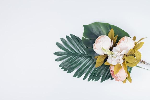 Sztuczne liście i bukiet kwiatów.