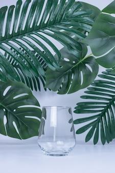 Sztuczne liście i puste szkło na białej powierzchni.