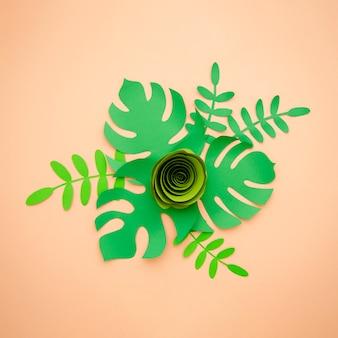 Sztuczne liście wycięte z papieru i zielona róża