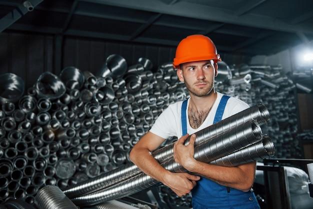 Sztuczne oświetlenie. mężczyzna w mundurze pracuje nad produkcją. nowoczesna technologia przemysłowa.