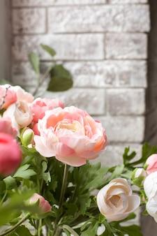 Sztuczne różowe kwiaty na białym murem
