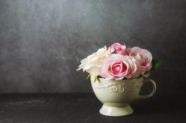 Sztuczne różowe kwiaty róży w vintage cup