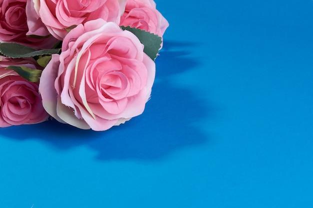 Sztuczne różowe róże na niebieskim tle.