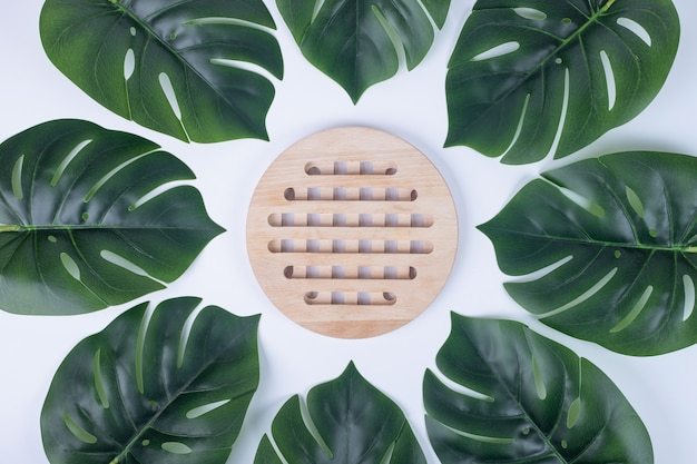 Sztuczne zielone liście i biała powierzchnia drewnianego talerza.