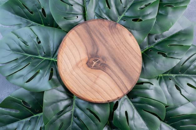 Sztuczne zielone liście wokół okrągłego drewna na niebiesko.