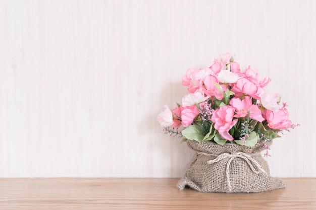 Sztucznego kwiatu bukiet w worku na drewnianym tle