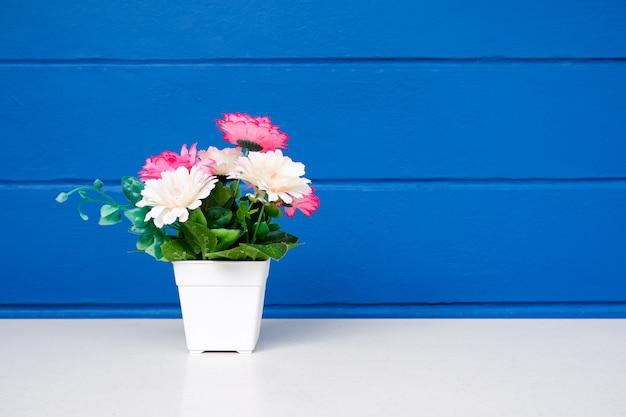 Sztuczni kwiaty w białym flowerpot na stole z błękitną kolor ścianą.
