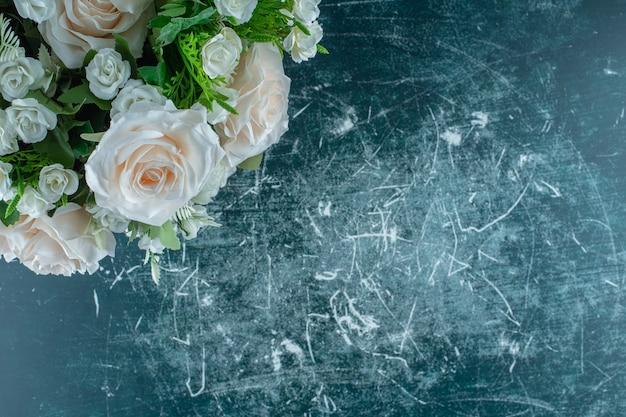 Sztuczny biały kwiat w paczce, na niebieskim tle.