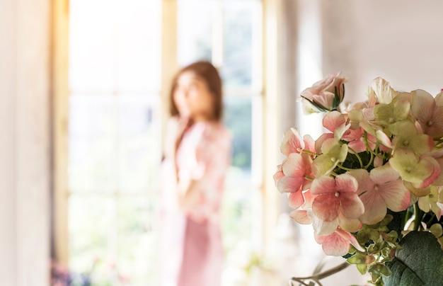 Sztuczny kwiat krzewu dekoracji domu i rozmycie kobiety