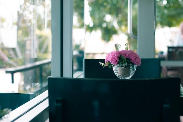 Sztuczny różowy kwiat na szklanym stole z kopii przestrzenią dla miłości tła