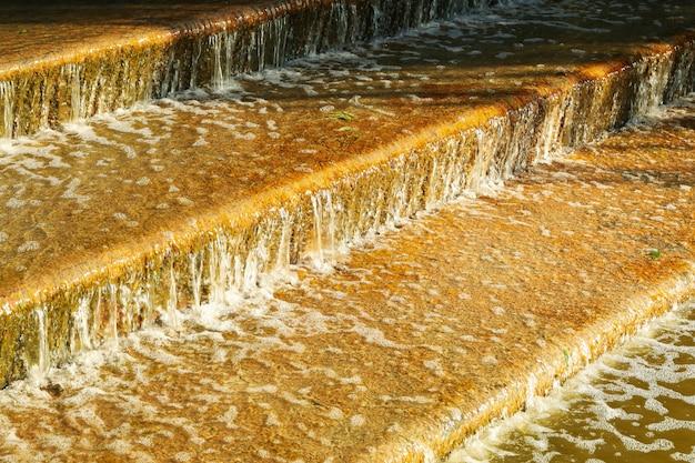 Sztuczny wodospad schodkowy w słoneczny poranek