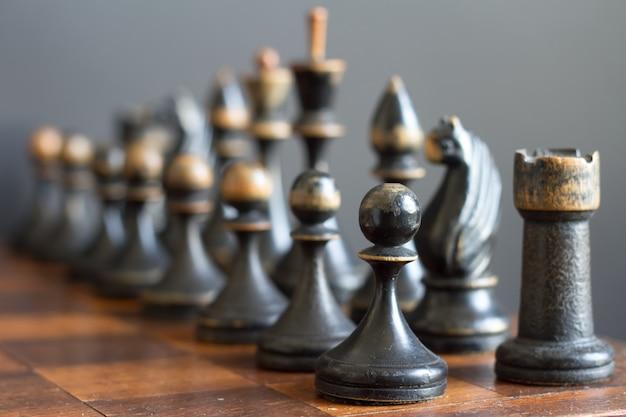 Sztuka drewniane szachy na starej szachownicy.