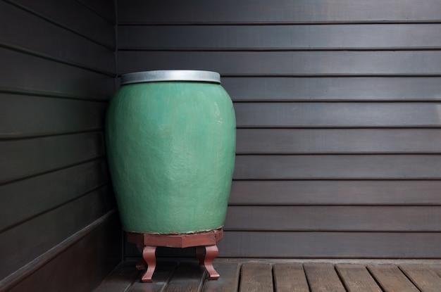 Sztuka duży zielony słoik ręcznie robiony ceramiczny na ścianie drewnianej