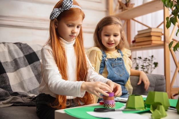 Sztuka. dwoje małych dzieci, dziewczynki razem w kreatywności domu. szczęśliwe dzieci robią ręcznie robione zabawki do gier