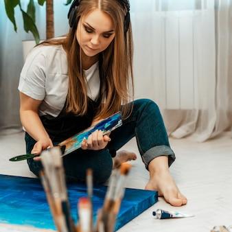 Sztuka, dzieło artysty. młoda piękna dziewczyna artysta maluje obraz i słucha muzyki przez słuchawki. warsztat artysty. rysunek i muzyka, farby. inwentaryzacja artysty. zbliżenie.
