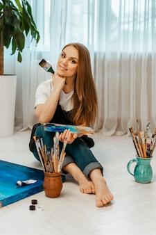 Sztuka, dzieło artysty. młody piękny artysta maluje obraz. warsztat artysty. proces kreatywności. rysowanie i malowanie. inwentaryzacja artysty. zbliżenie.