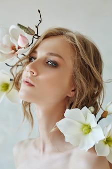 Sztuka dziewczyna blond kwiaty blisko twarzy. naturalne kosmetyki do pielęgnacji skóry, kobiety i naturalnego piękna skóry