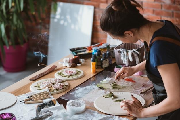 Sztuka gliny. rzemiosło ceramiczne. kreatywna atmosfera pracowni artystycznej. kobieta z narzędziami do modelowania w miejscu pracy.
